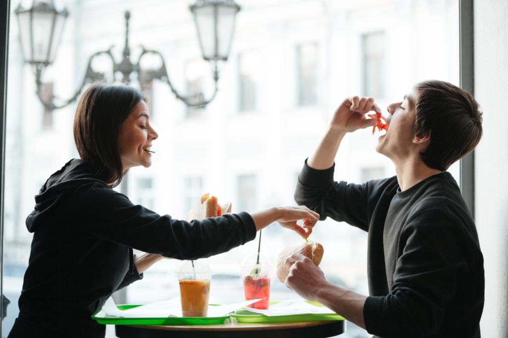 frere et soeur heureux entrain de manger un repas