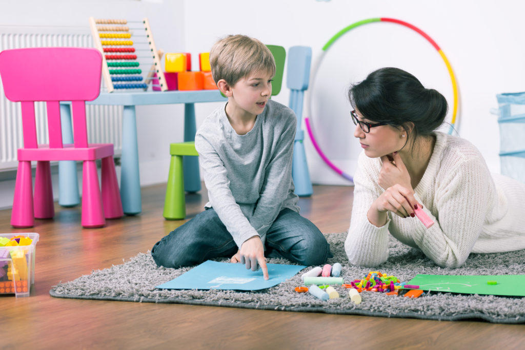 petit garçon joue avec une psychologue